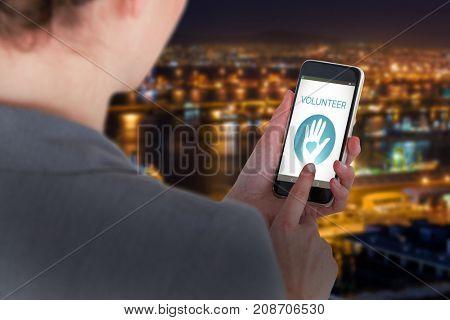 Close-up of businesswoman using mobile phone against illuminated harbor against cityscape