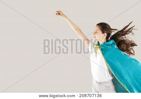 Happy Cheerful Female Child Wearing Superhero Clothing And Making Posing Ready To Fly On A Gray Back