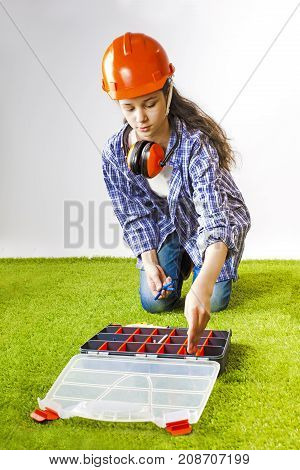 A young female construction worker chooses a tool for work in a box. Building concept