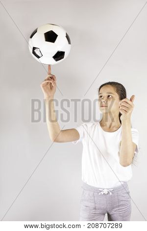 Cute Girl Football Player Junior Sportsman Twists On Finger Soccer Ball.