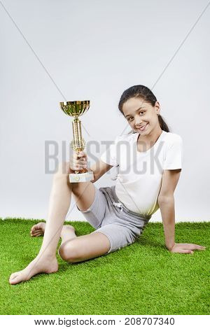 A Happy Sweet Girl Holding A Gold Cup.