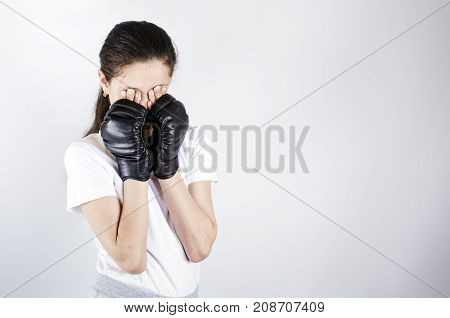 Young woman with boxing gloves. Gray background.