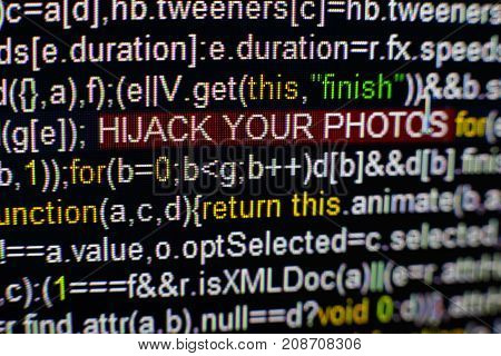 Macro photo of computer screen with program source code and highlighted HIJACK YOUR PHOTOS inscription in the middle. Computer script on the screen with virus in it. Cyber security concept.
