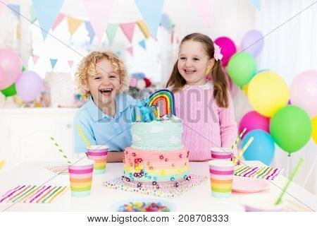 Kids birthday party with colorful pastel decoration and rainbow cake. Girl and boy with sweets candy and fruit. Balloons and banner at festive decorated table for child or baby birthday party.