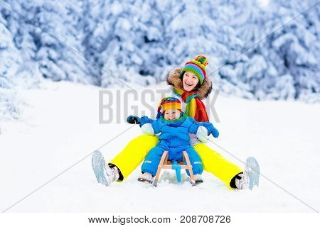 Mother And Baby On Sleigh Ride. Winter Snow Fun.