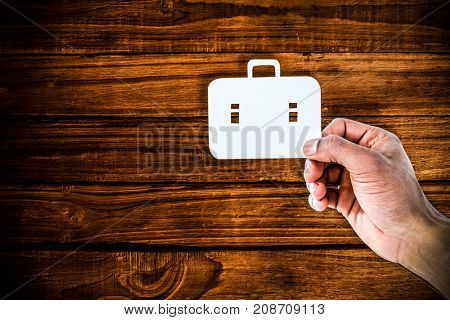 hand holding a schoolbag against overhead of wooden planks