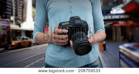Mid section of female photographer holding digital camera against blurry new york street