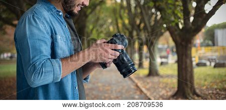 Smiling male photographer using camera  against footpath amidst trees at park