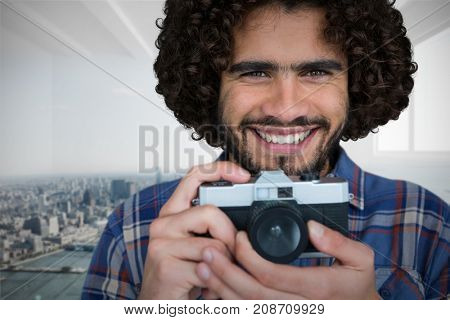 Close up portrait of smiling photographer holding camera  against city scene in a room