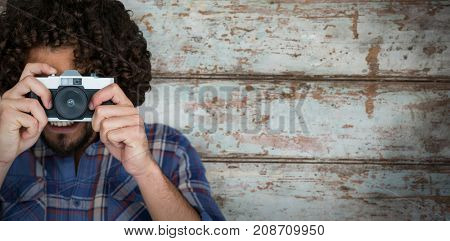 Close up of photographer taking picture with camera  against wood background