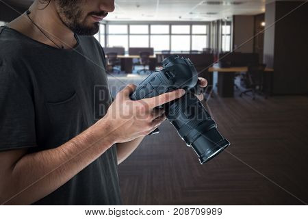 Young photographer operating digital camera  against table and empty chairs in office