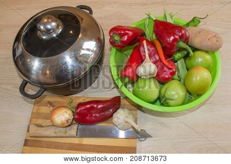 fresh organic vegetables onion potato green french beans garlic and pepper on wooden table. Fresh organic vegetables casserole on table