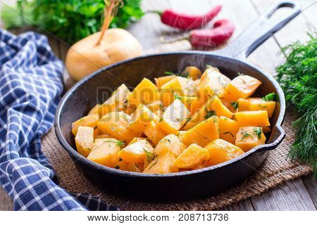 Turnip baked in the frying pan on a wooden background