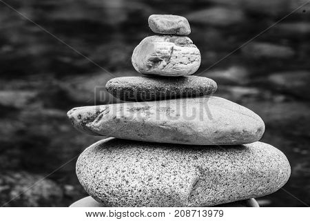 Small and large rocks balanced together. A black and white image of a well balanced rock cairn.
