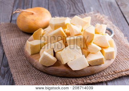 Cubes turnips on a chopping board on a wooden background