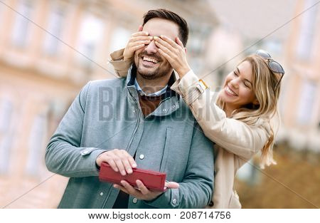 Woman surprising his boyfriend with a gift.Young woman with giftbox closing his boyfriend eyes to make a surprise for him.