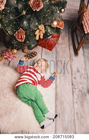 Cute child in the pajamas spend time with family at home interior on background of the Christmas tree. Little kid boy celebrate Christmas and New Year.