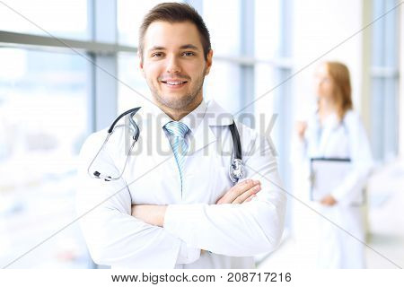 Smiling doctor waiting for his team while standing upright.