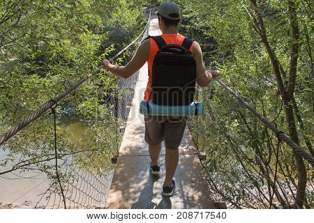 Eco tourism and healthy lifestyle concept. Young hiker boy with backpack. Active hikers. Traveler travel on the suspension bridge go trekking together