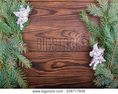 Winter concept of a green spruce branch on a brown wooden background on the sides with angels