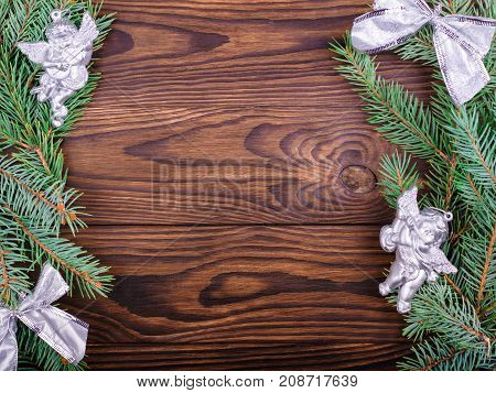 Winter concept of a green spruce branch on a brown wooden background on the sides with angels and bows