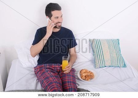 Man Talking On Phone In Bed.