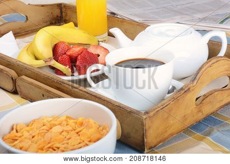 Breakfast tray with coffee orange juice cereals and fruits.