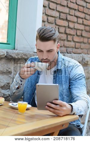 Young Man In Coffee Shop Cafe Using A Tablet.