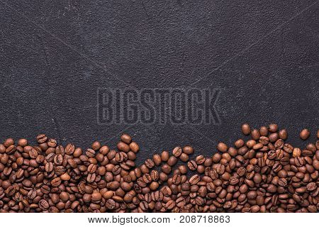 Coffe beans on black slate background. Coffe over black.