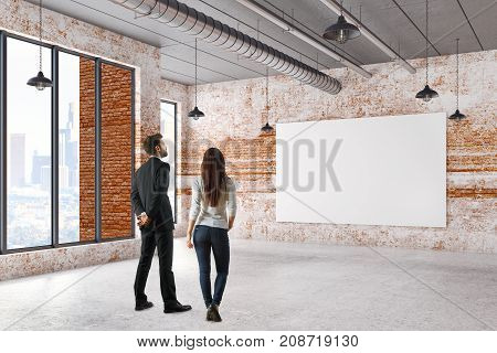 Back view of young businessman and woman looking at empty banner in grunge interior with city view. Gallery exhibition concept. Mock up 3D Rendering