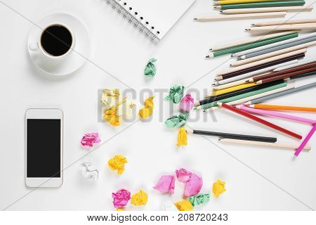Top view of messy white office desk with colorful supplies cellular phone coffee cup and other items. Close up mock up