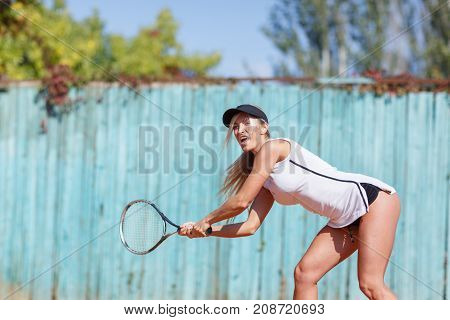 Young beautiful woman is playing tennis. He beats the pitch. In full growth. The concept of sport.