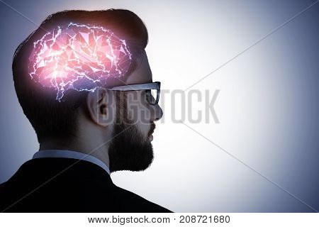 Side portrait of handsome caucasian busiessman in glasses with glowing digital brain on gray background. Artificial mind concept