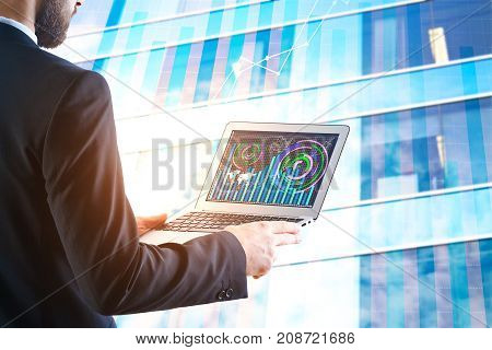 Side view of businessman using laptop with business chart. City building background. Financial growth concept. Double exposure