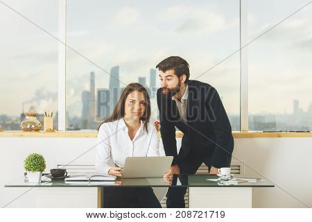 Portrait of playful male and female working together at modern office desk. Meeting teamwork discussion and togetherness concept
