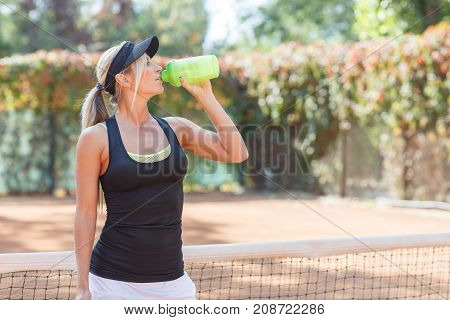Pretty young beautiful tennis player drinks water with closed eyes. The concept of sport.