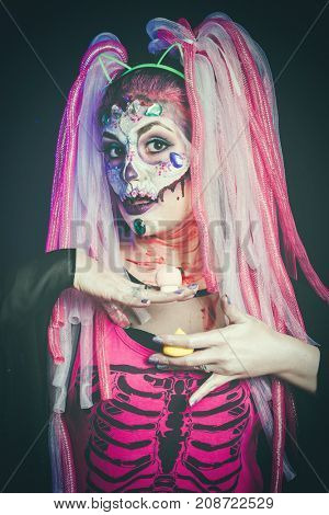 scary halloween woman with sugar skull makeup offering  candy mushrooms studio shot