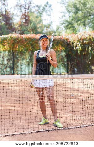 Beautiful tennis player, stands on a tennis court with a racket. In full growth. The concept of sport.