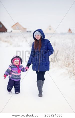 Snowy winter day mother and child outdoors.