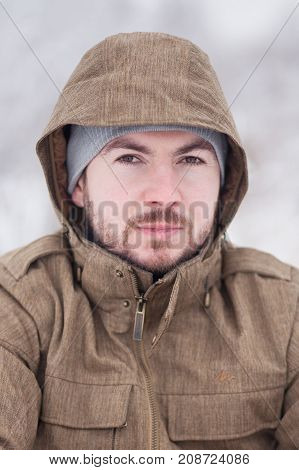 Outdoor Portrait of a handsome bearded man dressed in winter clothes handsome man wear coat and grey hat.