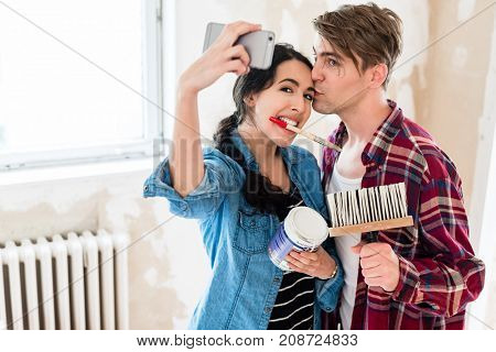Young couple in love making a funny selfie while working together to the interior renovation of their new home