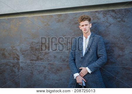 Businessman in gray coat. It stands against the background of the wall. The concept of career and entrepreneurship. Close-up.