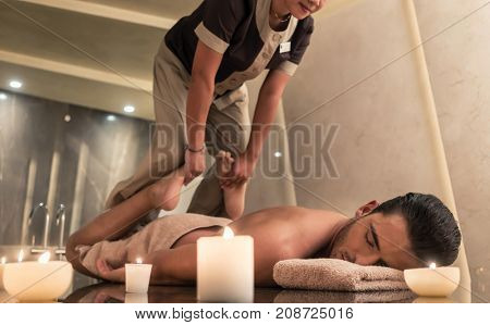 Thai massage practitioner massaging young man through traditional stretching techniques in a luxury spa and wellness center
