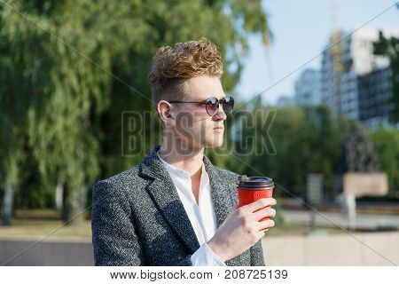 A young guy in the city wearing glasses, holding coffee in the hands of a tree in a gray coat. Close-up.