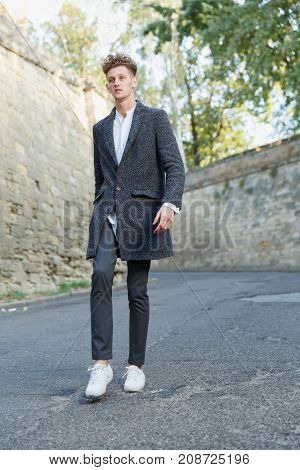 Young man in gray coat, white shirt, confident, success. Against the background of a high wall in the street. In full growth.