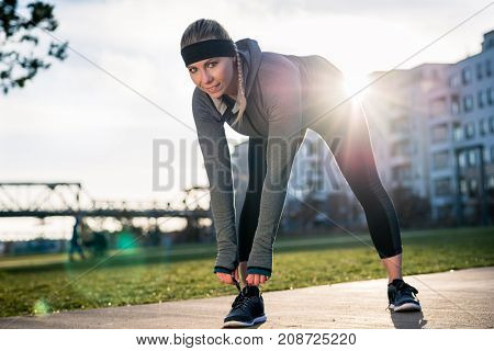 Full length of a beautiful young woman looking at camera with a confident smile, while tying the shoelaces of her sport shoes outdoors in the park