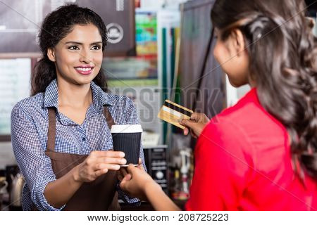 Indian woman customer paying coffee  for takeout with credit card