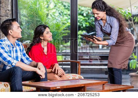 Indian waitress taking orders of two customers in cafe or restaurant