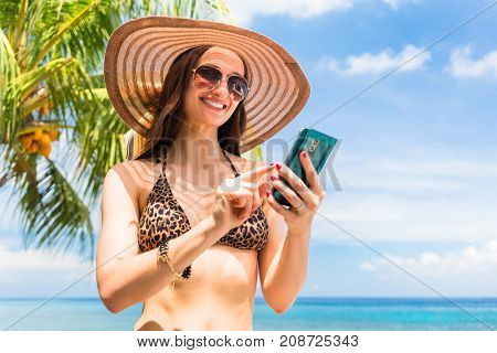 Tourist woman on vacation with smart phone on palm beach needs data roaming