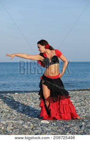 Dancer woman in black and red suit with fan dancing on seashore, gesture